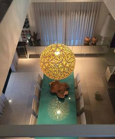 The glowing orb of the David Trubridge SOLA pendant light sees itself in the reflection in the table below. Click image for where to buy or to sign up for our newsletter.
