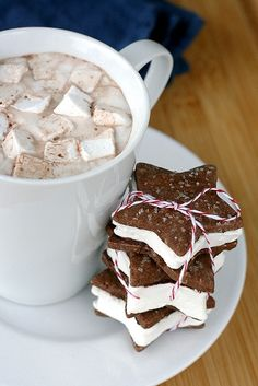hot choclate th marshmellows  star biscuit wth cream inside.