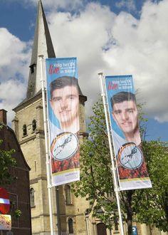 In Bilzen hangen overal vlaggen met de foto van Courtois om de EK-wedstrijden op groot scherm te promoten. (Johnny Geurts)
