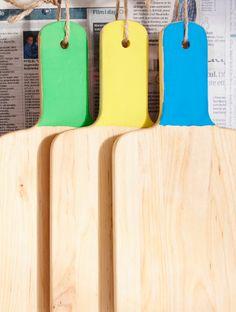 Drei IKEA Schneidebretter aus Holz mit unterschiedlich bemalten Griffen.