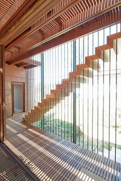 Timber staircases are suspended on thin steel rods, creating slotted views of the outdoors.