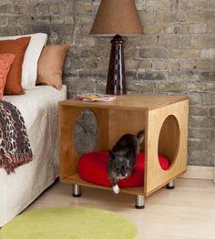 Une table de nuit en bois avec un panier à chat intégré