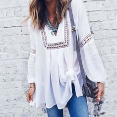 Gorgeous billowing white chiffon pairs with lace inset details on this top. Designed with long draped sleeves, a v-neck button bust, and a flowy tunic fit. Perfect paired with jeans for a chic winter