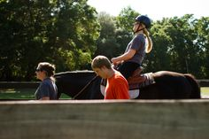 HOrses Helping PEople volunteer Alex Hendrix (right) and barn manager Kaylie Madore (left) walk with Lauren Ault while she rides Lila during a hippotherapy session at the HOPE farm in Archer on April 8. Ault was diagnosed with a brain stem tumor at the age of 20, which left her wheelchair-bound.