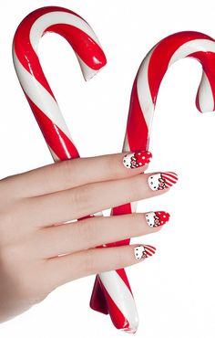 Check out this amazing Christmas Hello Kitty inspired nails. Coated in bright red nail polish, you can see Hello Kitty's face peeking out of the bottom of the nails. The tips are painted with white polka dots over a base of red polish with stripes representing sweet candy canes.