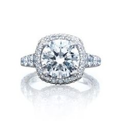 Channels of graduating diamonds curve into the ceiling of this distinctive engagement ring, featuring two rows of blooming diamonds to enhance the cushion-cut center diamond.
