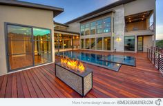 Beautiful wood finish. Nice modern fire feature on all wooden pool deck.