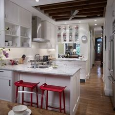 love the mix of white painted cabinets, warm wood tones and the red stools