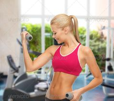 young sporty woman with light dumbbells at gym ...  athlete, athletic, beautiful, biceps, body, bodybuilding, care, center, coach, diet, dieting, dumbbells, equipment, exercise, exercising, facility, figure, fit, fitness, girl, gym, happy, health, indoor, lifestyle, light, loss, muscles, perfect, person, personal, physical, pumping, result, shape, shaping, slimming, smiling, sport, sportswoman, sporty, stamina, strength, strong, trainer, training, weight, woman, workout, young