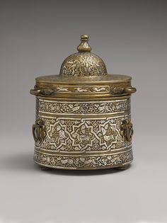 Inkwell with Zodiac signs. Date: early 13th century. Geography: probably Iran. Culture: Islamic. Medium: Brass; cast, inlaid with silver, copper, and black compound. Dimensions: H. 5 7/8 in. (14.9 cm) H. w/o lid: 3 5/8 in. (9.2 cm) Diam. 4 9/16 in. (11.6 cm). Accession Number: 59.69.2a, b. The base of the inkwell is decorated with signs of the Zodiac with Planetary Lords.