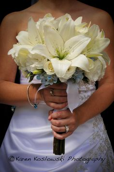 white lily, roses and lisianthus accented with pale blue hydrangea