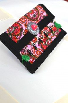 Pochette en tissu velours lisse imprimé. Intérieur velours lisse rose. Galon en velours noir tout autour. Deux pompons verts.Taille 25x14,5 cm