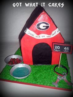 """Georgia Bulldog Doghouse - I did this HUGE groom's cake (weighed almost 30 pounds) for HUGE Georgia Bulldog fans! I came up with the idea of doing a doghouse, complete with a shingled roof, and then the details made it super personalized and really special. The banner says, """"Go Dawgs, sick 'em woof woof woof,"""" which is a popular cheer during the games. I did a scoreboard reflecting the blackout game where UGA beat Auburn 45 to 20! I made silver dog bowls, filled with water and food. The dog…"""