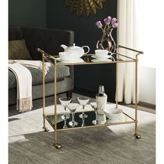 Ready to serve party guests in style, the two-tiered Felicity bar cart in gold-finished iron is dressed up with mirrored glass top and lower shelf.