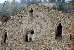 Photo taken in Arquà Petrarca, one of the most beautiful towns in Italy, where the poet which took its name and heritage Unesco from 2011 through the hills in the province of Padua in Italy. In the picture you see the top, with a mullioned window and two side windows of a medieval villa with a wall built of blocks of stone sunlit outlined by a hedge and the green of the hill behind trees.