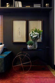 Decoração neutra e elegante, Casa Cor, estante preta com nichos e adornos, carrinho preto com vasos de vidro e flores, quadros.