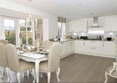 David Wilson Homes - Leicester. French style kitchen with french linen upholstered chairs and a white painted french table. Again, I think DWH have done well with the weathered oak flooring tiles - this table set up would have looked really well in the Layton design too. The massive windows are beautiful and the finished garden makes the photo.