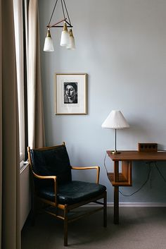 Pearl grey wall, vintage teak chair and table, minimalistic lamp and framed art print. Sharon Radisch
