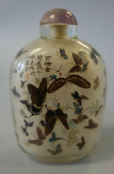 A Chinese glass snuff bottle. Inside painted on all sides depicting an abundance of butterflies. Signed on the shoulder with a red seal mark and Chinese calligraphy.