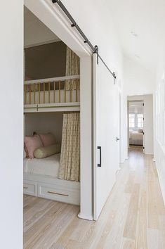 A sliding barn door on rails opens to a bunk room featuring a white built-in bunk bed accented with brass guard rails and yellow privacy curtains hung from brass rods. Bunk Bed With Slide, Bunk Beds Built In, Build In Bunk Beds, Wood Bunk Beds, Basement Bedrooms, Home Bedroom, Bunk Bed Rooms, Bunk Bed Designs, Dream Rooms