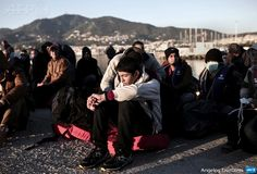 GREECE, Lesbos Island : A group of migrants from Syria sit  upon arrival to Greece at the port of Lesbos island on April 16, 2015. The  decision was made at an emergency cabinet meeting chaired by Prime Minister  Alexis Tsipras. Since Greece bolstered controls along its land border with  Turkey, along the Evros River, illegal immigrants have turned to the maritime  route between Turkey and the Greek islands in the Aegean Sea, notably Lesbos,  Samos, Kos and Chios. 2015 started with a major…