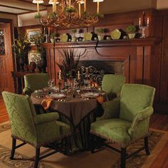 Oh...I love the warm wood, table set up for dining in front of the fireplace, the antler chandelier, and the way the three small plates on the mantle echo the color of the chairs.