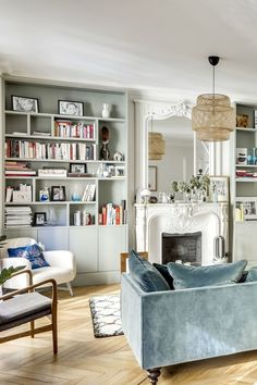 Home Interior Illustration Parisian living room with faded blue sofa and white marble fireplace, built-in bookshelves, hardwood floors via CoteMaison Studio 85 By Casaromani et Conscience Parisian Decor, Quirky Home Decor, Elegant Home Decor, Elegant Homes, Cheap Home Decor, Parisian Style, Paris Living Rooms, My Living Room, Apartment Living