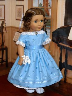 Marie Grace models a lovely blue cotton print dress, with lined bodice and short straight sleeves. The dress has a bodice with a wide neckline trimmed in cotton lace with a cameo at center front, and the sleeves have the same lace with sheer ribbon trim with tiny bows on each sleeve. The full gathered skirt has a narrow and wide sheer ribbon band at the hem.The waistband is a length of blue silk ribbon to tie in a bow at the back. The dress closes in back with ultra-thin velcro under…