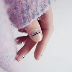 Nail Artist Frédérique Olthuis gave her negative nail a subtle shine. To get the look, paint a clear base coat and let dry. Add a thin, black stripe at the half moon. When tacky, add metallic flat sequins to the strip and seal it with a clear top coat. Design by
