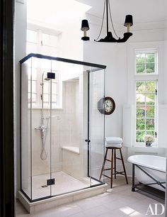 A Washington, D.C.–area home designed by Darryl Carter has a clean-lined shower flooded with natural light. The fittings are by Waterworks, and the clock—which dates to the 19th century—is from Lee Stanton Antiques.