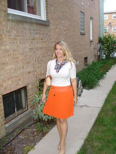 Tie necklace, white shirt, pony belt, orange skirt, faux osterich purse, neutral heels.