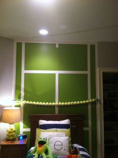 I painted a tennis court in a kids room and used a ping pong net to mount on the wall and I put tennis balls on it.
