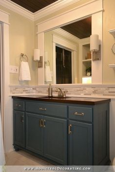remodeled bathroom with DIY vanity made from stock oak cabinets, mosaic accent tiled backsplash, and mirror with sconces