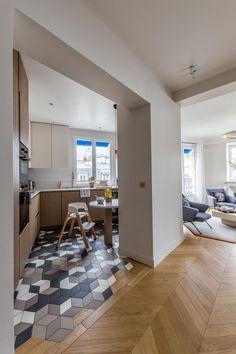 Les différences de sols créent une démarcation entre la cuisine et le salon, sans pour autant réduire les espaces.