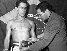 18/11/1960: Éder Jofre recebe o cinturão de campeão mundial peso-galo da AMB (Associação Mundial de Boxe) após nocautear o mexicano Eloy Sanchez, no 6º round