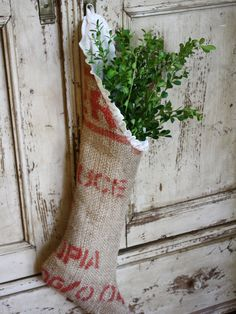 DIY: Natural Stockings -- Pull in traditional holiday colors with this burlap-sack stocking covered in bright red lettering. Fresh greenery pokes out of the top for a rustic look. Would love to make some of these but as Christmas stockings! Noel Christmas, Primitive Christmas, Country Christmas, Winter Christmas, Christmas Swags, Xmas, Natural Christmas, Burlap Christmas Stockings, Burlap Stockings