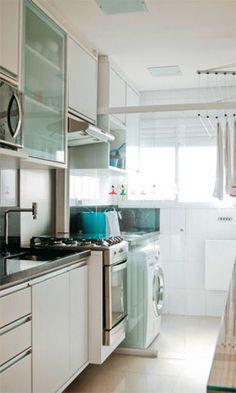 Para aproveitar na cozinha a luminosidade que vem da área de serviço, os moradores separaram os ambientes com uma porta de correr de vidro. Cada vareta do varal sobe e desce individualmente, facilitando a tarefa de pôr as roupas para secar. Projeto da arquiteta arquiteta Marina Barotti.