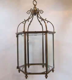 Large English six sided lantern in the original brass finish and in the Georgian style, complete with the original bevelled glass panels. c 1910-1920 www.antiquelightingcompany.com