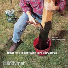 Brushing wood preservative on a cedar fence post.