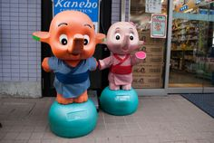Sato-chan (orange) and Satoko-chan (pink), mascots for Japan's Sato Pharmaceuticals...the fiberglass figures usually stand outside most drugstores in Japan...because they're wanted by collectors in Japan and overseas, some store owners have taken to chaining them to prevent theft...
