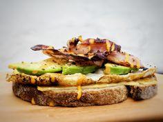 Oerbrood, gesmolten oude kaas, gebakken ei, avocado & bacon