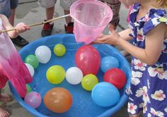 """Find the Matching Pearls Game – Fill a small plastic pool halfway with water. Place lots of mini bouncy balls in the water. I purchased mine from a dollar store. Blow up some balloons and throw them on top of the water to make it a little more challenging. Have the guest use a small fishing net or butterfly net to find and scoop out matching """"pearls."""""""