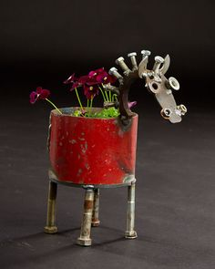 Made of recycled industrial scrap metal, this pony planter will fit standard medium size pots (~6-7). The planter will drain water out the bottom.