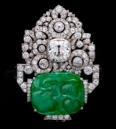 An art deco jadeite jade and diamond brooch, Mauboussin, 1929  designed as a jadeite jade flower pot carved with gourds and fruiting vines, centering a cushion-cut diamond among old mine, old European, and transitional-cut diamond flowers, accentuated by buff-top onyx and black enamel; unsigned, no. 025099; cushion-cut diamond weighing approximately: 6.35 carats; estimated remaining diamond weight: 5.10 carats; mounted in platinum