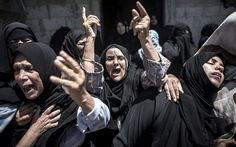 Palestinian women mourn during the funeral of the Abu Muamar family in Khan Younis, southern Gaza Strip. The family of three were killed in an Israeli airstrk