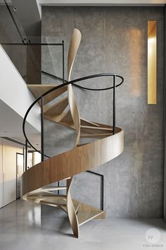 This intriguing timber staircase set before a moody expanse of concrete has immense visual appeal with its beautiful almost helix-like central twist and it's smooth sweeping exterior. By YYDG InteriorDesign. - Architecture Daily