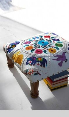 Low footstool upholstered in richly embroidered elephant motif. Fixed around edges with brass studs and finished with polished wooden legs. Fairtrade product. 45.5cm x 45.5cm H20cm  Code T5ST136  $122.07