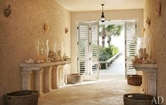 Limestone consoles topped with hurricane lamps flank a passageway with rough stucco walls and a scored-cement floor.