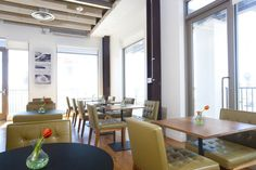 Classic leather chairs in olive green flank the cafeteria space at Innocean Worldwide Advertising.  By Kenneth Brown Design.