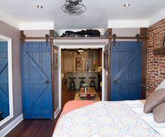 blue, sliding barn doors seen across a brick and white-trimed bedroom with hardwood floors, open to show the living space in the next room